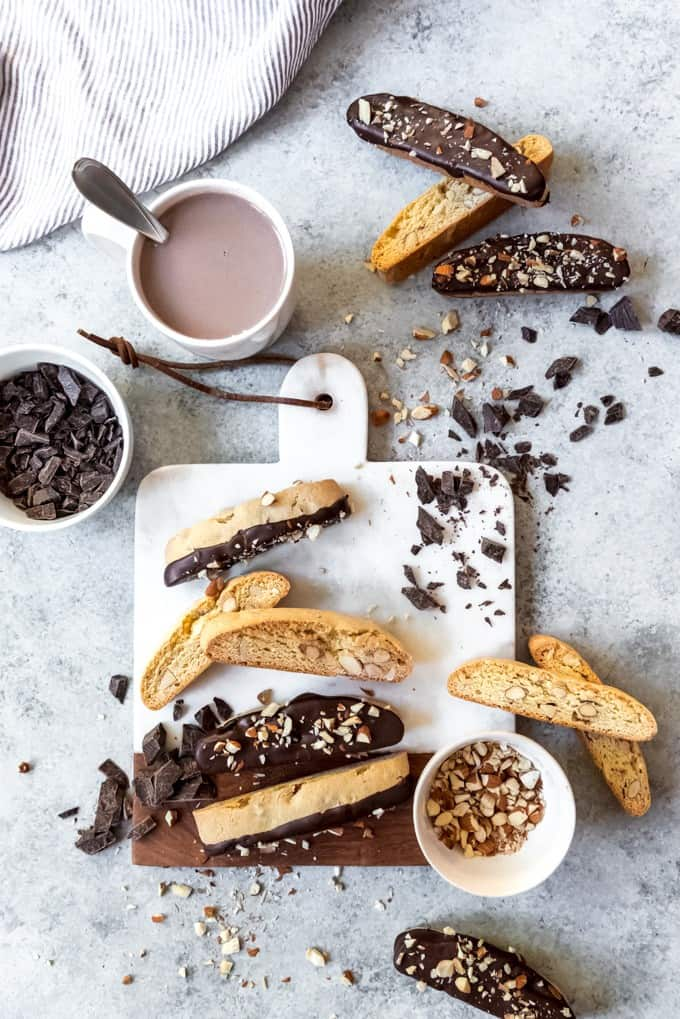 An image of a cutting board with biscotti piled on it and a mug of hot chocolate nearby for dunking.