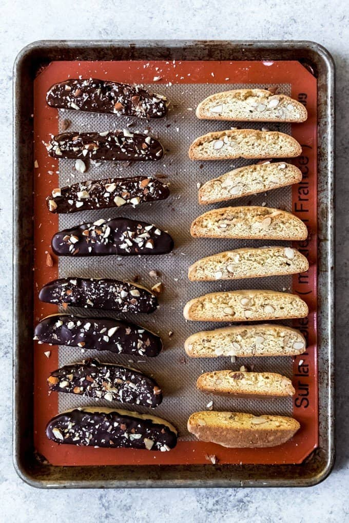 An image of Italian almond biscotti cookies on a baking sheet, some covered with dark chocolate.