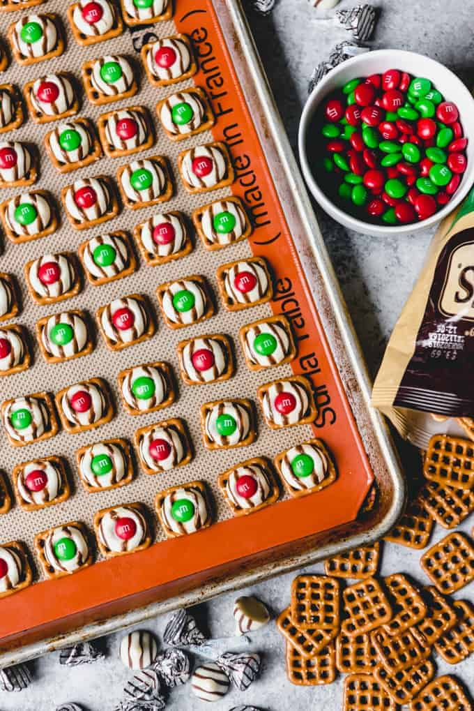 An image of bite-size Christmas treats made festive with red and green M&M's pressed into melted Hershey's hugs on top of square pretzels.