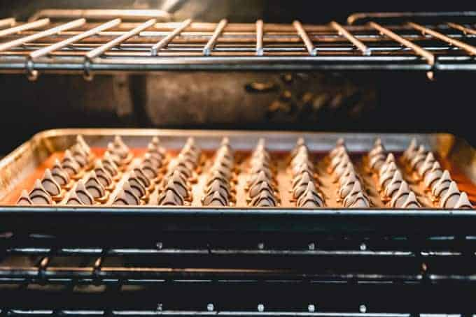 An image of pretzels and Hershey's hugs on a baking sheet in the oven, melting to make easy Christmas pretzels treats.