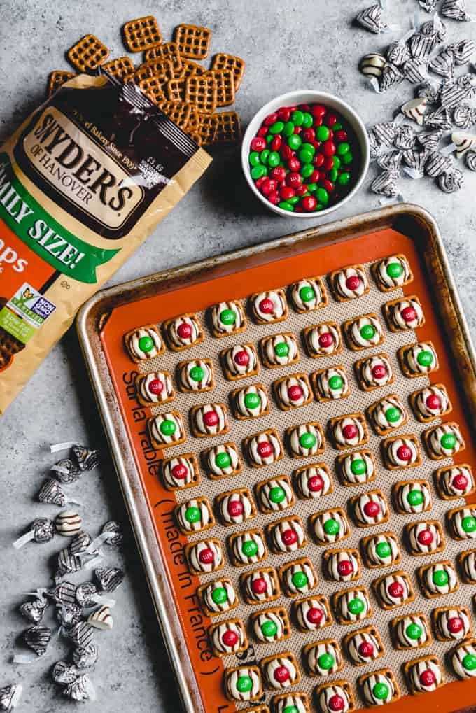 An image of Christmas hugs made with square pretzel snaps, melted Hershey's hugs, and red and green Christmas M&M's.