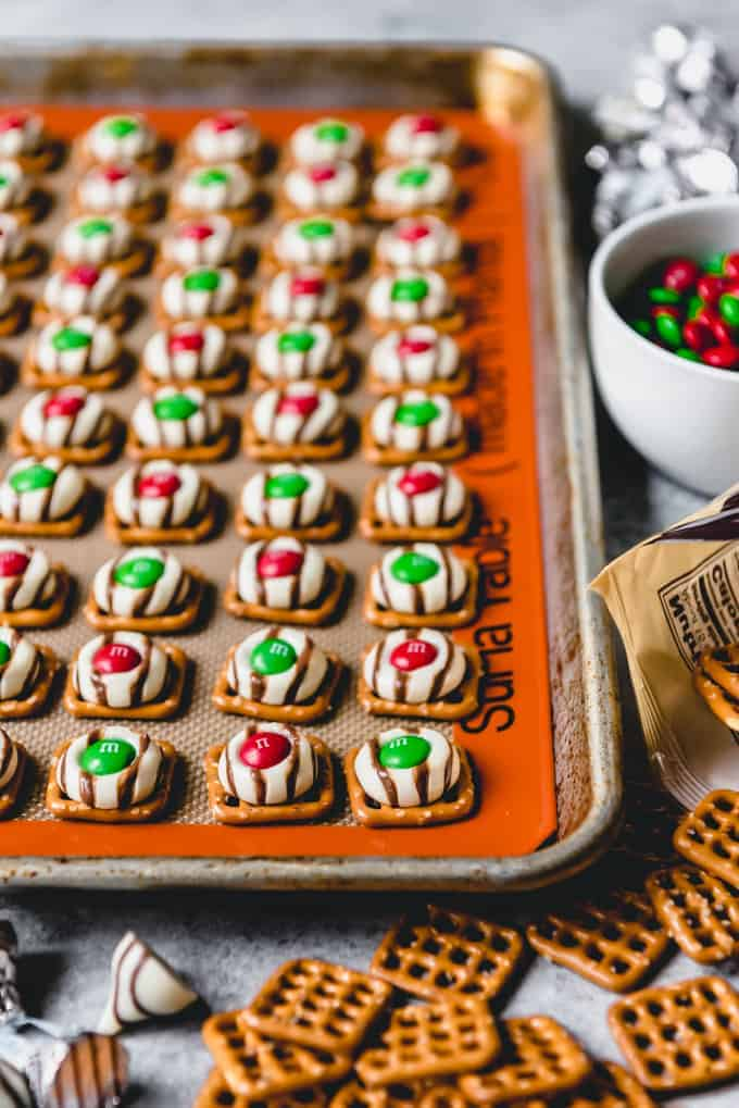 An image of easy pretzel hugs with red and green Christmas M&M's on a baking sheet with a silpat mat.