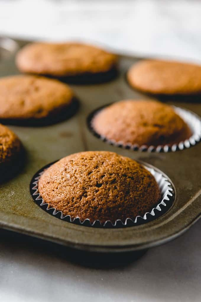 An image of unfrosted gingerbread cupcakes cooling in a muffin tin.
