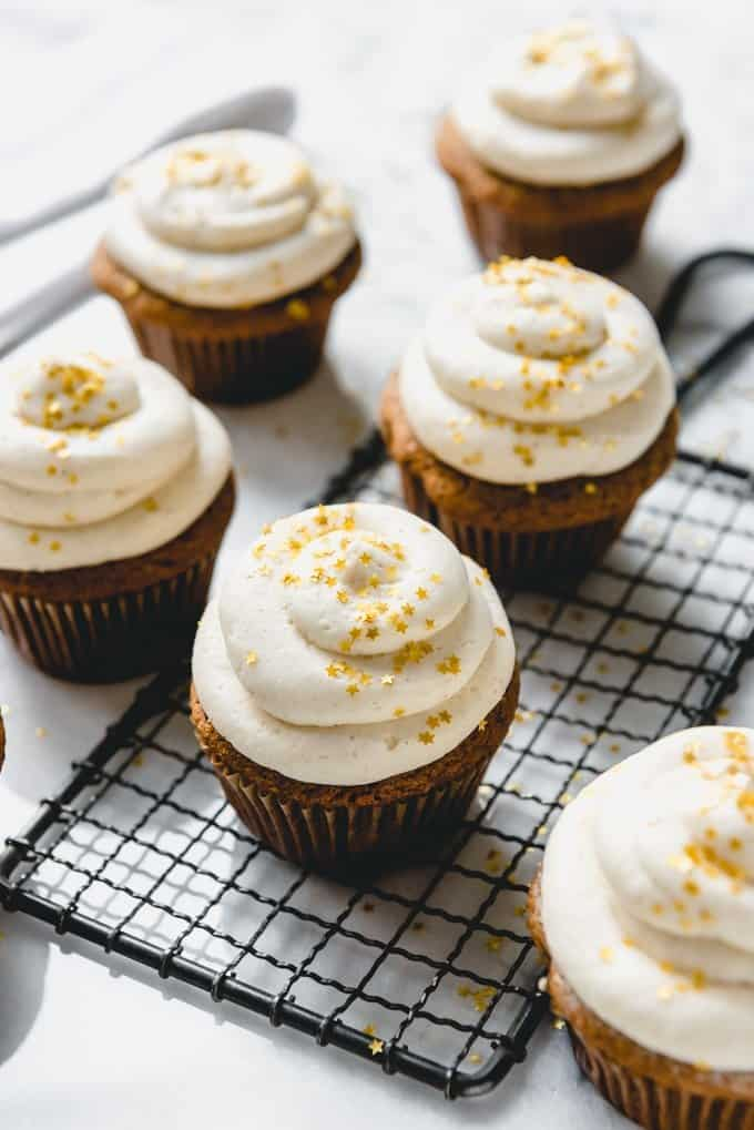 An image of homemade gingerbread cupcakes with eggnog buttercream and golden star sprinkles.