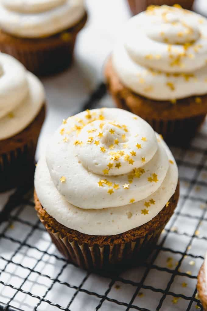 An image of gingerbread Christmas cupcakes frosted with swirls of eggnog buttercream frosting and sprinkled with gold star sprinkles.