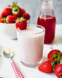 a cup of homemade strawberry milk with a glass of strawberry syrup in back and fresh strawberries to the sides