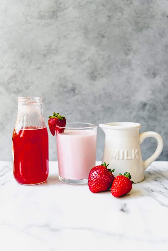 An image of a simple strawberry syrup next to a glass of strawberry milk.