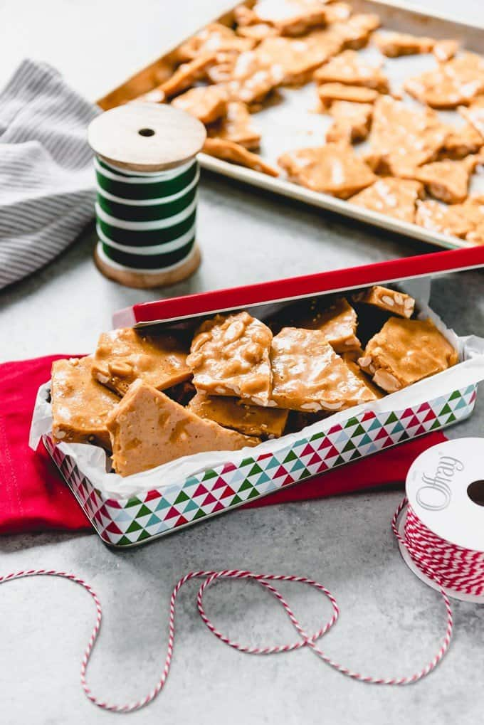 An image of a festive tin full of easy peanut brittle candy made from scratch.
