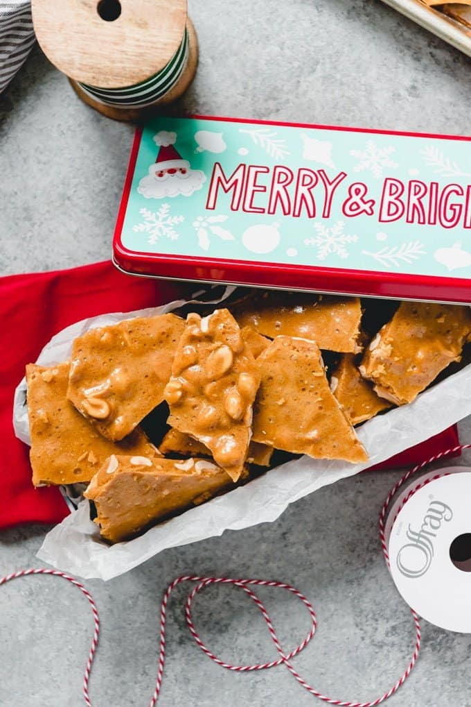 An image of a festive tin full of homemade peanut brittle candy.
