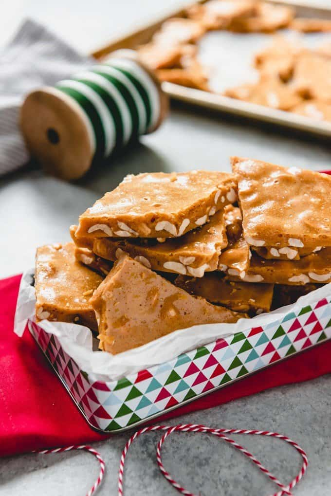 An image of old-fashioned peanut brittle in a Christmas tin for gift-giving.