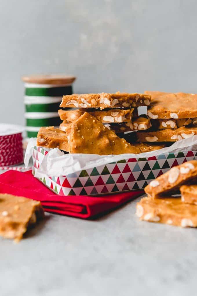 An image of a festive tin full of old-fashioned homemade peanut brittle candy made from scratch.