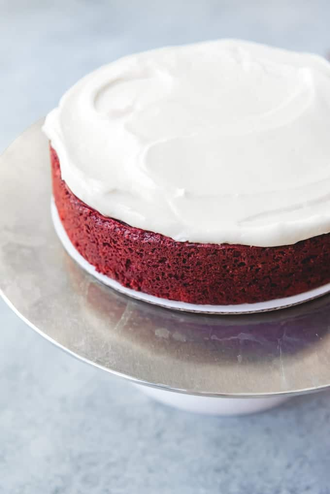 An image of a single layer of red velvet cake that has been frosted with cream cheese frosting.