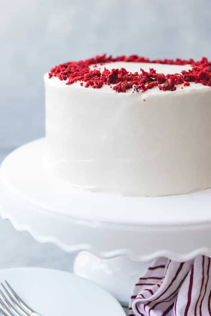 An image of a frosted red velvet cake with cream cheese frosting and red velvet crumbs sprinkled on top.