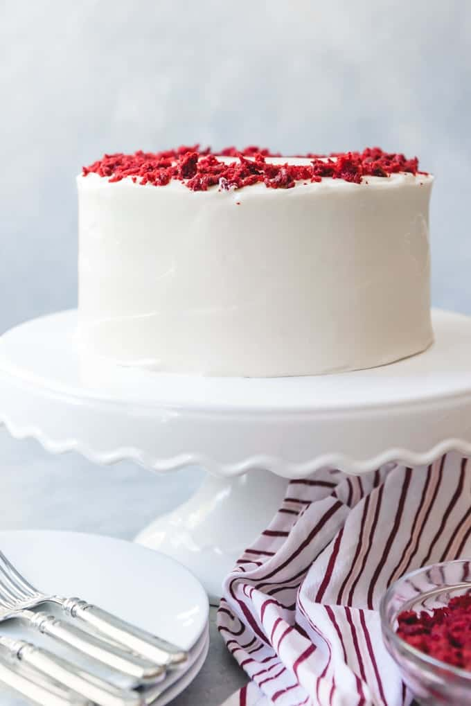 An image of a made from scratch red velvet cake with cream cheese frosting and red velvet crumbs sprinkled on top.