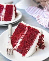 two slices of Red Velvet Cake on white plates with a fork