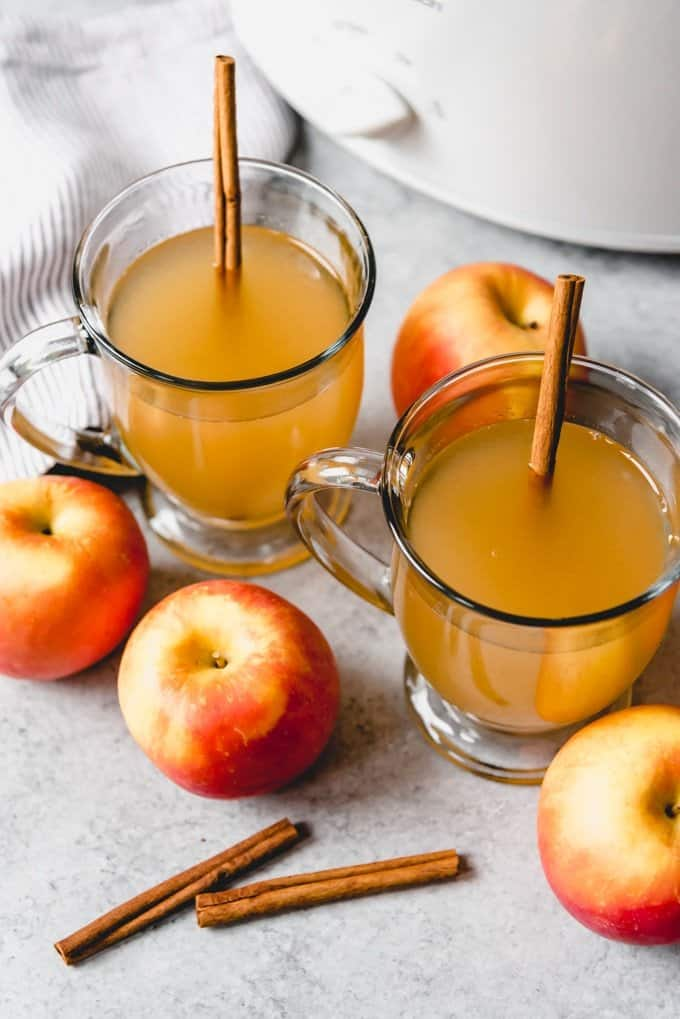 An image of crock pot apple cider in glass mugs with apples and cinnamon sticks around them.