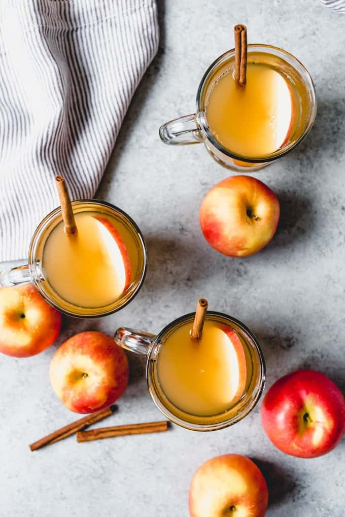 an aerial view of glasses of apple cider with garnishes surrounded by apples and a few cinnamon sticks