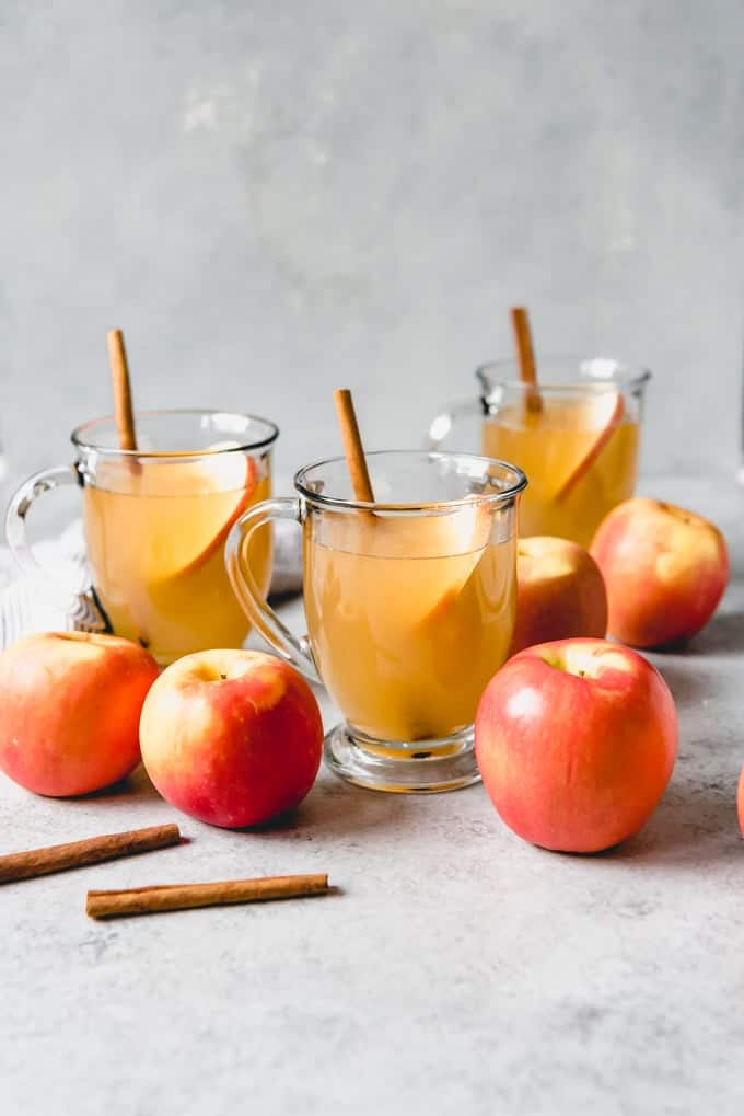An image of three glass mugs of apple cider with cinnamon sticks in them.