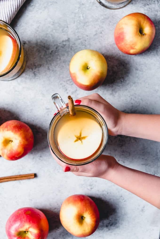 An image of hands holding a mug of apple cider with an apple slice and cinnamon stick in it for garnish.