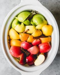 a slow cooker with fresh fruit and cinnamon and cloves inside