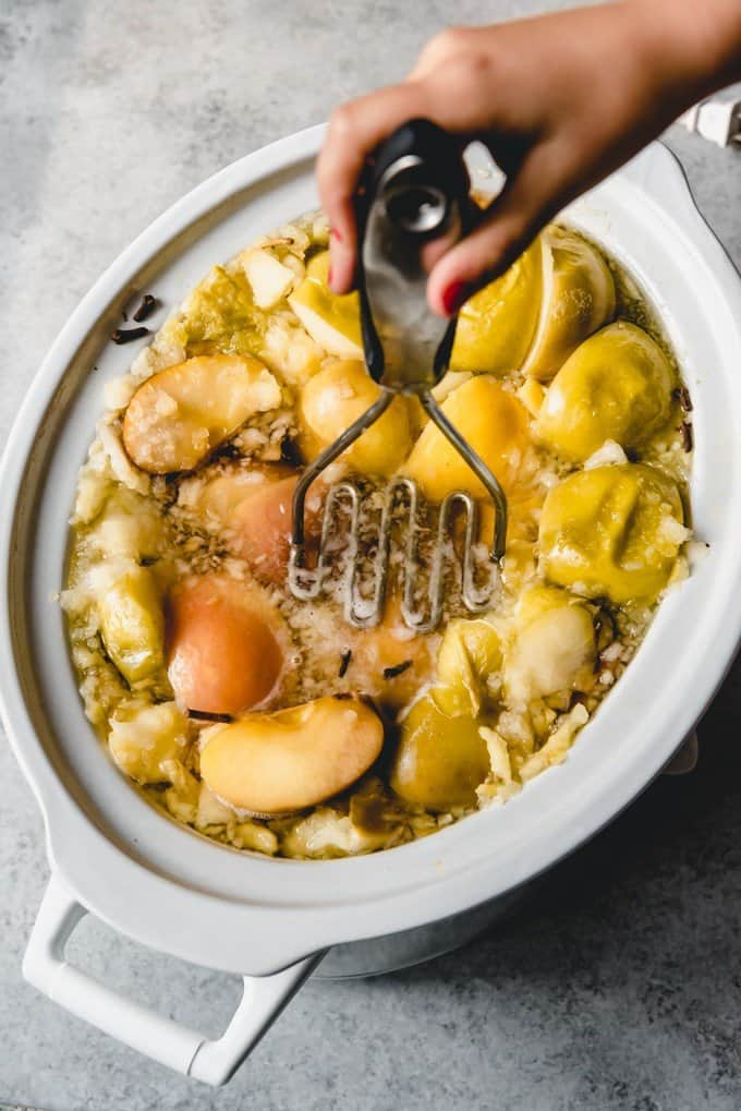 An image of a potato mashed mashing apples in a slow cooker.