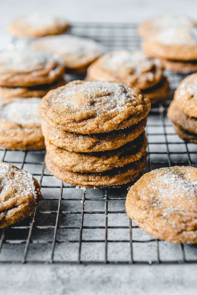 An image of a stack of soft ginger molasses cookies on a wire cooling rack.