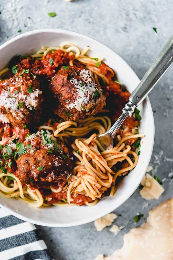 Made with both ground beef and ground pork, with Italian herbs, Parmesan cheese, and a flavorful, easy, homemade spaghetti sauce, this is the best spaghetti and meatballs recipe ever and it is classic Italian-American comfort food at it's best.