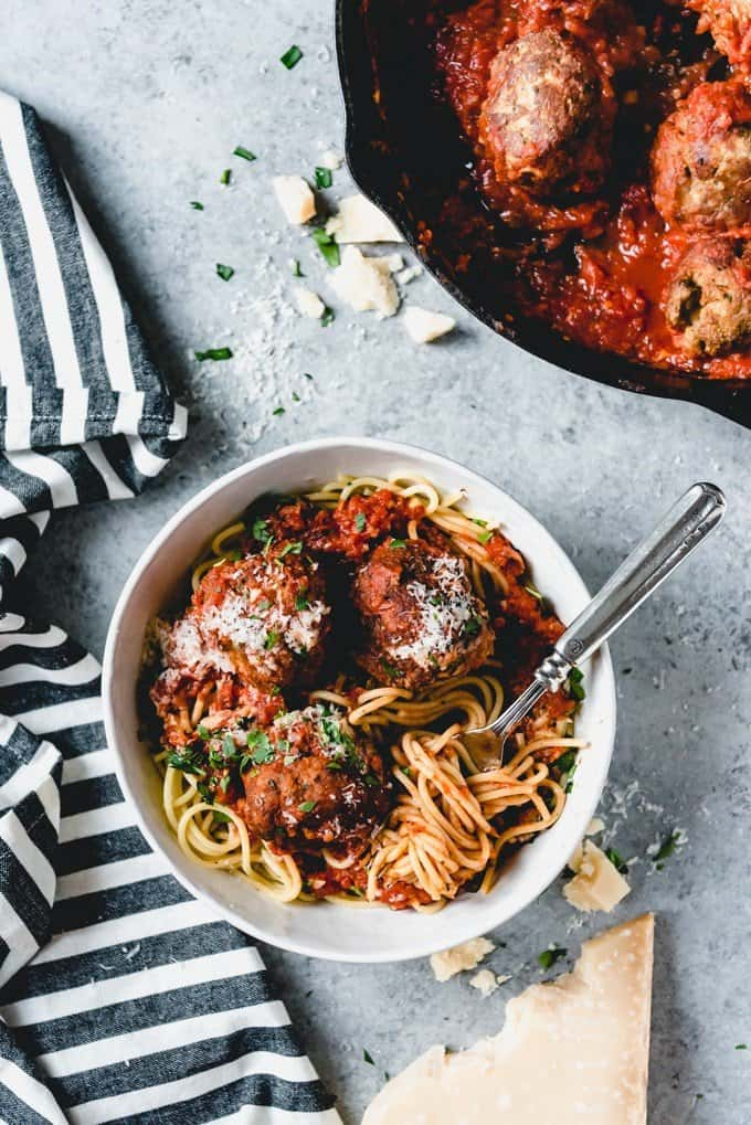 An image of a bowl of spaghetti and meatballs made from scratch and served family style with plenty of freshly grated Parmesan cheese on top.
