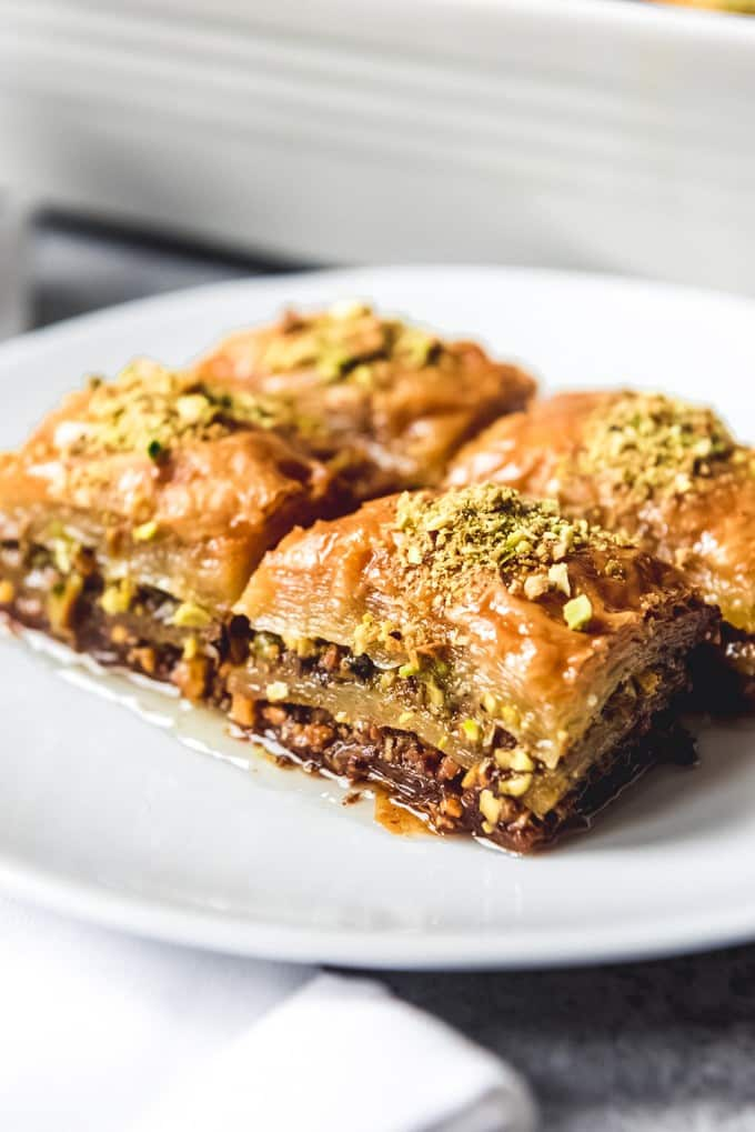 An image of four squares of Turkish pistachio baklava made with a sweet sugar syrup.