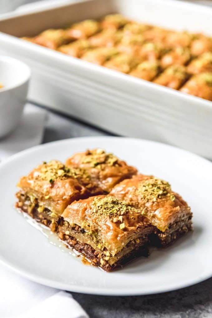 An image of fistikli baklava (Turkish baklava) made with pistachios, on a white plate in front of a pan full of baklava.