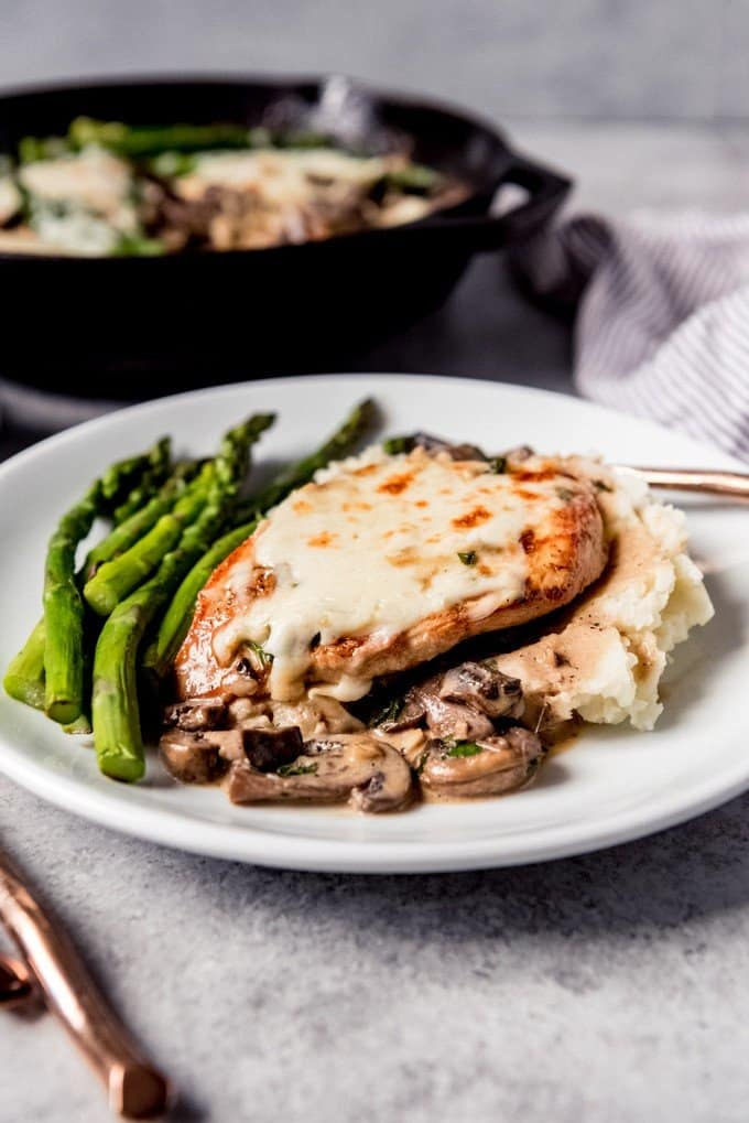 An image of a white plate with a Cheesecake Factory copycat recipe for Chicken Madeira with mushrooms, asparagus, and mashed potatoes.