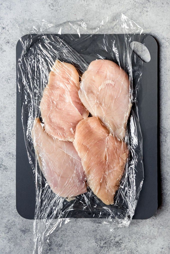 An image of chicken breasts pounded thin between plastic wrap using a meat mallet.
