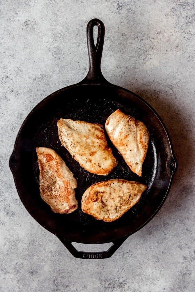 An image of browned, pan-seared boneless skinless chicken breasts in a cast iron skillet.
