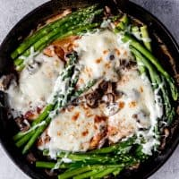 Fresh mushroom Madeira sauce, tender crisp asparagus, and melted cheese pair with tender, juicy sautéed chicken breasts to make this Chicken Madeira recipe that is one of our favorite family dinners that is special enough for weekend cooking or holidays, but easy enough for weeknights when we are craving something different from the norm. It's touted as one of the most popular menu items at the Cheesecake Factory. Once you've tasted a bite it's easy to see why!