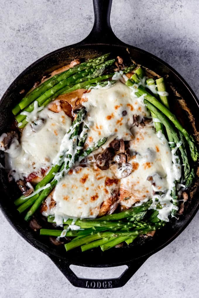 An image of a skillet of asparagus, pan-seared chicken breasts, melted mozzarella cheese, and a creamy Madeira wine sauce for Cheesecake Factory Chicken Madeira made at home.