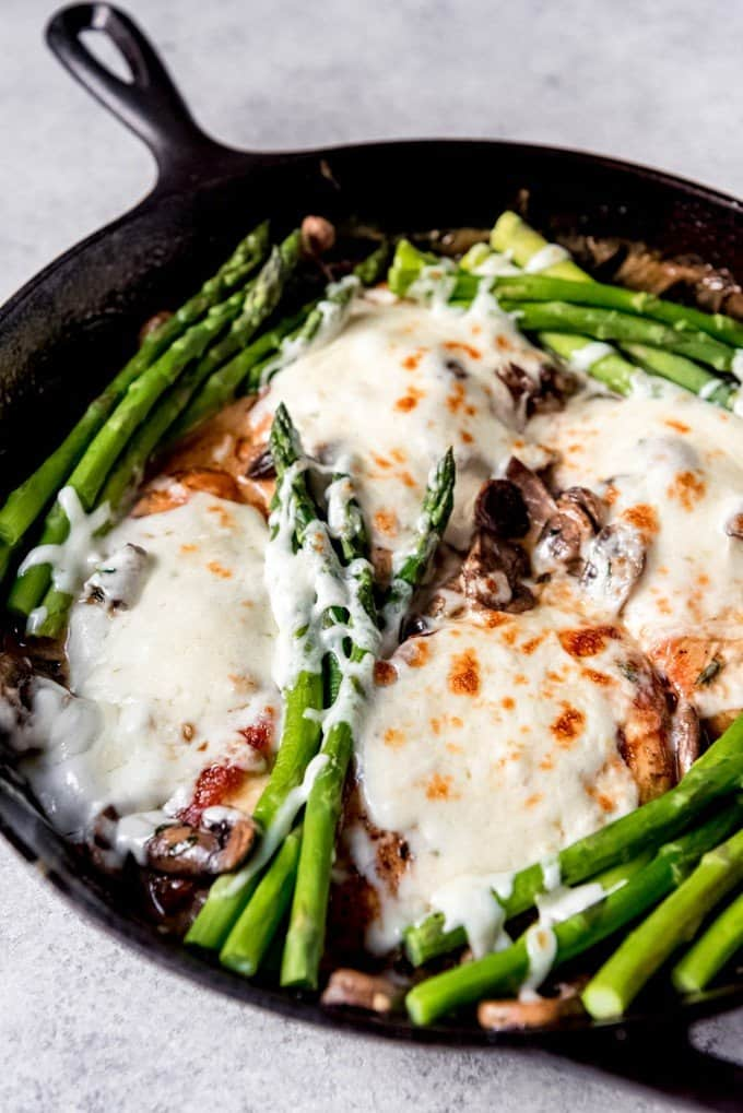An image of a skillet of Chicken Madeira topped with blanched asparagus and melted mozzarella cheese.