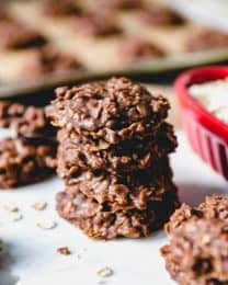 stacked no bake cookies with a baking tray full of more in the background