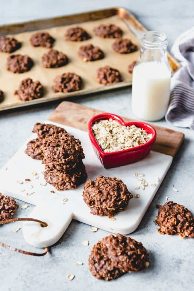 An image of chocolate peanut butter no bake cookies with a glass of milk and a bowl of oats next to them.