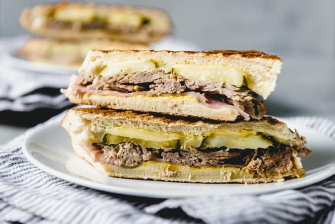 A Cuban sandwich is loaded with roast pork, deli ham, dill pickles, yellow mustard, and Swiss cheese on soft Cuban bread and toasted.