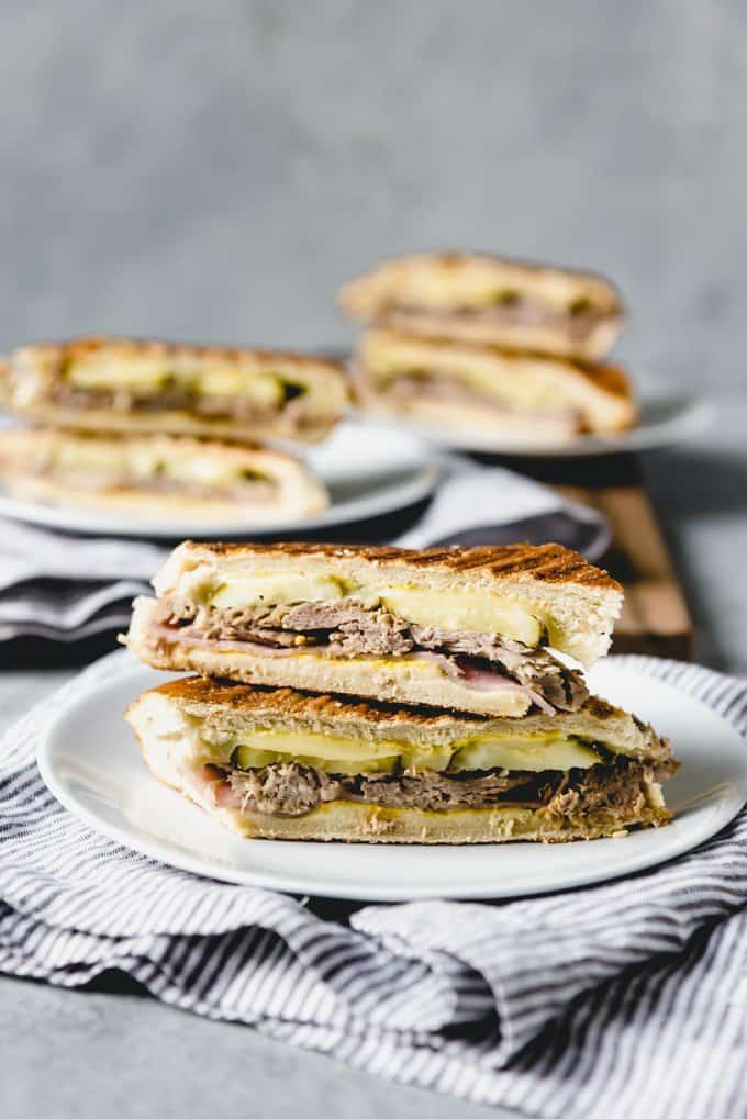 If you have never tried Cubanos [a traditional Cuban Sandwich recipe], then you are in for a treat!  Break out your panini press or a frying pan and cook up these ham and mojo pork filled sandwiches that are also loaded with melted Swiss cheese, yellow mustard, and dill pickles!