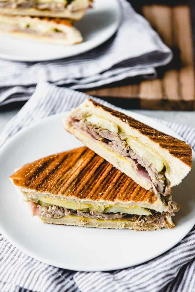 An image of a hot cuban sandwich, also known as a cubano sandwich, cut in half on a plate.