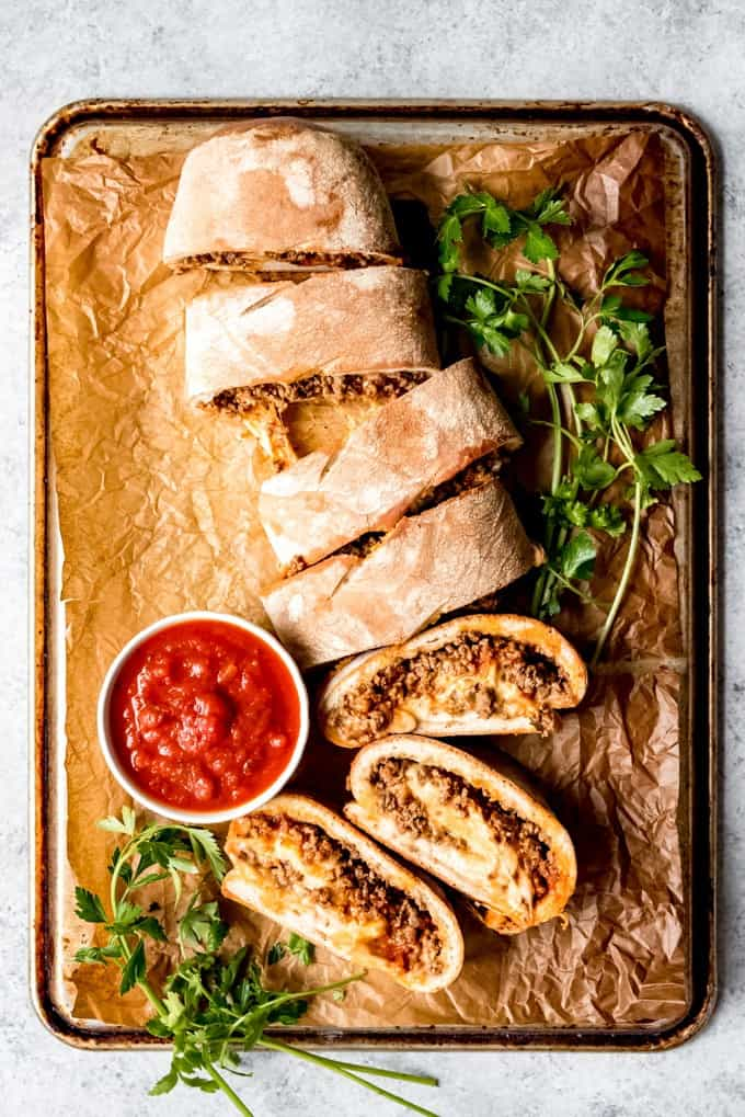 An image of a ground beef and cheese stromboli cut into slices with marinara sauce for dipping.