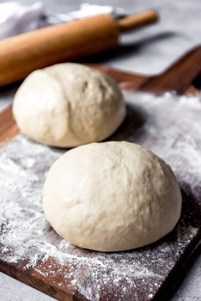 An image of two balls of homemade pizza dough.