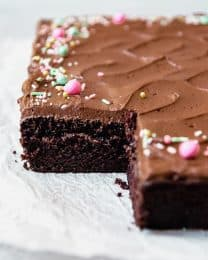 Frosted Chocolate cake with sprinkles missing a slice