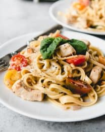 """One Pot Bruschetta Chicken Pasta is a full-flavored pasta dish made with tender chicken, garlic, fresh basil, and bright cherry tomatoes. It's an easy weeknight meal made entirely in one pot with all the flavors of my favorite bruschetta (pronounced """"broo-sketta"""", not """"broo-schetta"""")."""