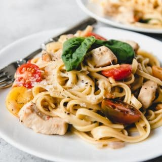 "One Pot Bruschetta Chicken Pasta is a full-flavored pasta dish made with tender chicken, garlic, fresh basil, and bright cherry tomatoes.  It's an easy weeknight meal made entirely in one pot with all the flavors of my favorite bruschetta (pronounced ""broo-sketta"", not ""broo-schetta"")."
