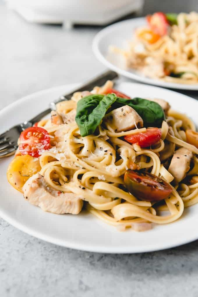 An image of a plate of creamy bruschetta chicken pasta made in one pot with cherry tomatoes, fresh basil, and plenty of Parmesan cheese.
