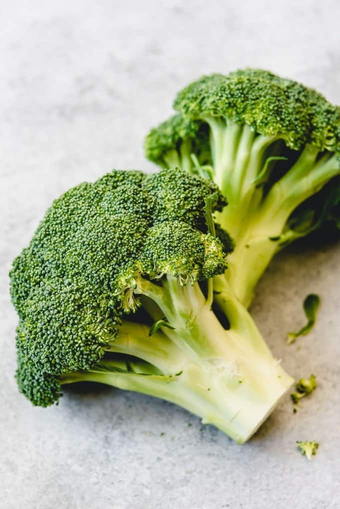 An image of two heads of broccoli ready to be chopped into florets and roasted in the oven.
