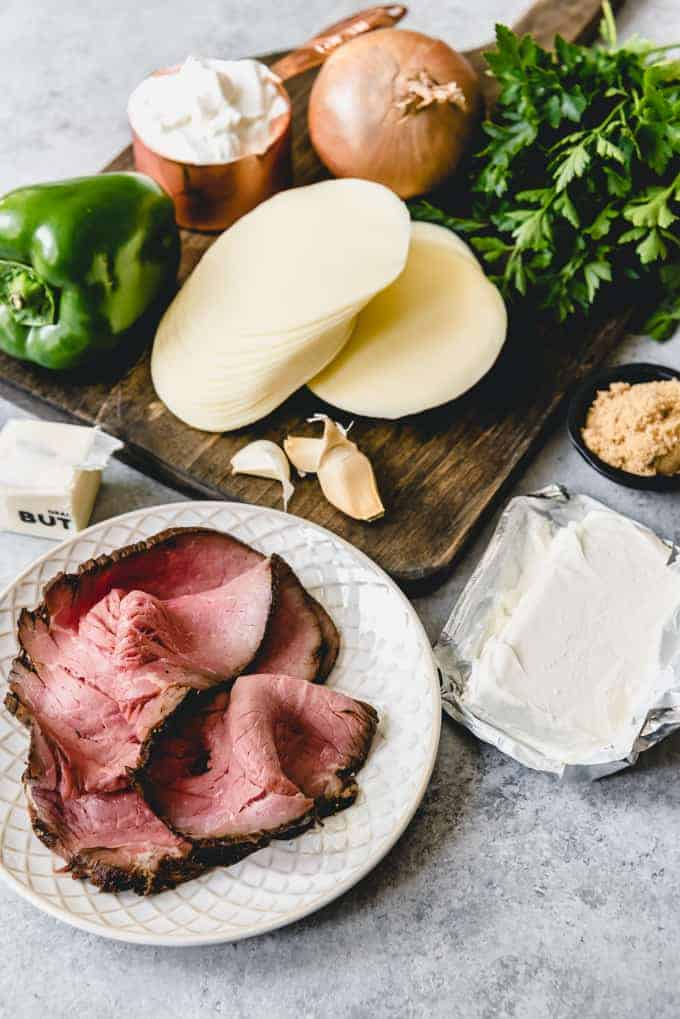 An image of the ingredients for Philly Cheese Steak Dip set out on a cutting board including provolone cheese, green pepper, garlic, onion, sour cream, cream cheese, brown sugar, butter, and deli-sliced roast beef.