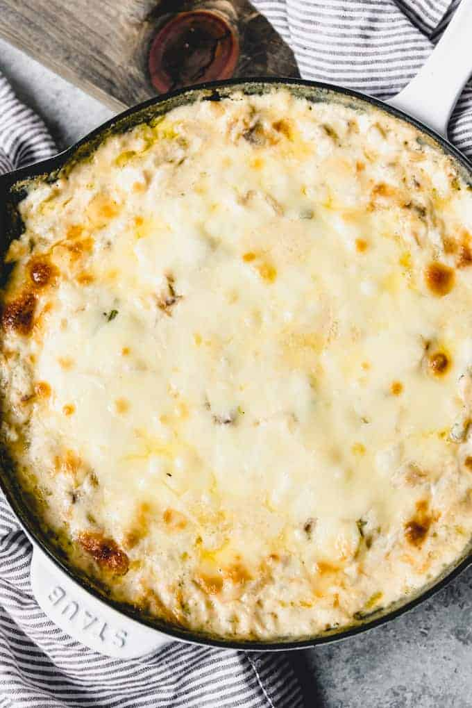 An image of a skillet filled with hot cheesy dip for a party appetizer or snack.